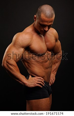 Muscular man standing poses on dark background