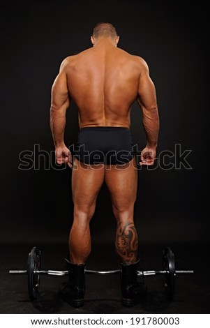 Muscular man standing shows his back with dumbbell on dark background