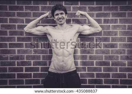 Muscular man stood against brick wall flexing his bicep muscle. He has his top off, and is very lean and muscular, his six pack prominently on show.  He is smiling.