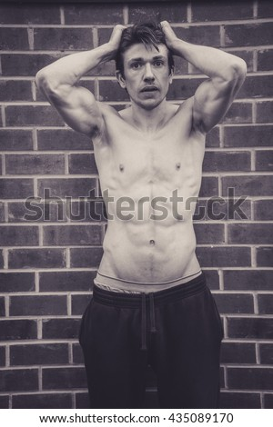 Muscular man stood against brick wall flexing muscles, and giving a pose as if to say he is losing his mind, or out of control. He has his top off, and is very lean and muscular, his six pack on show.