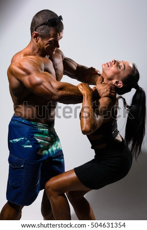 Muscular man strangling a beautiful woman. A man with a naked torso in conflict with woman