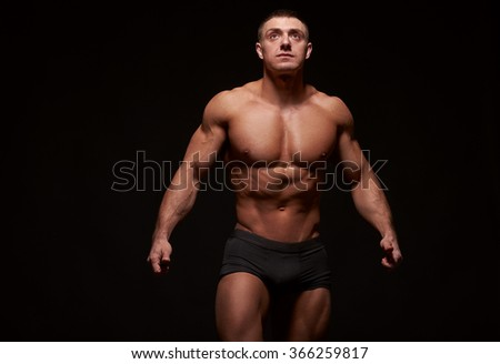 Muscular man stretching his arms out against of black background. Studio shot