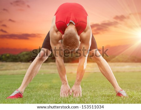 Muscular man stretching out in beautiful scenery - stock photo