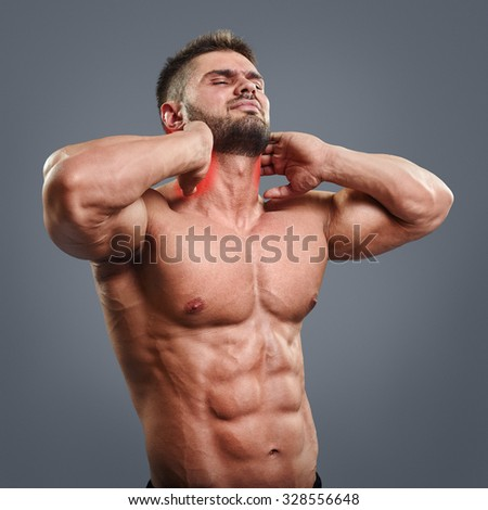 Muscular man suffering from neck pain. Front view over gray background