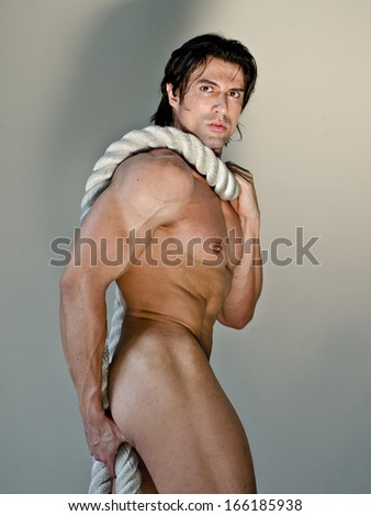 Muscular man totally naked with heavy, big rope around neck, looking at camera - stock photo