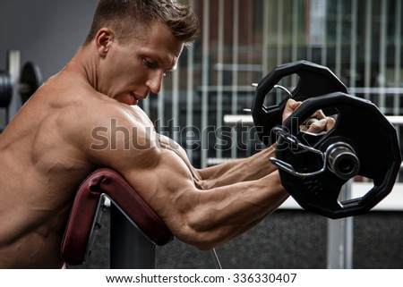 Muscular man training his arms in gym