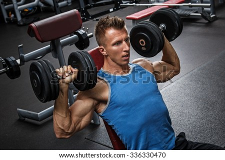 Muscular man training his shoulders with dumbbells