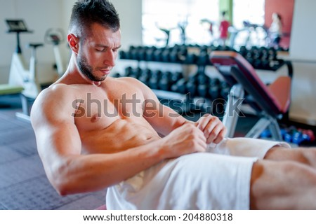 muscular man training in the gym, abs workout on the bench - stock photo