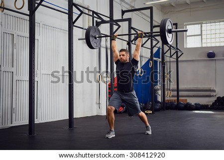 Muscular man training lunges with barbells over head - stock photo