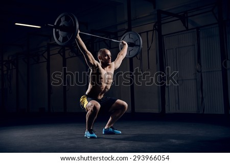 Muscular man training squats with barbells over head - stock photo