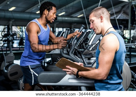 Muscular man using elliptical machine with trainer at gym - stock photo