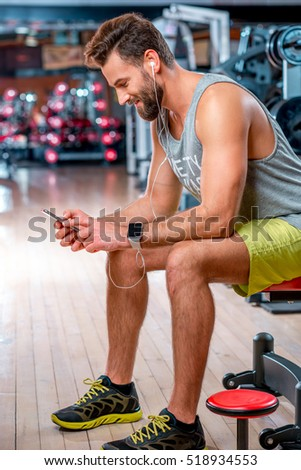 Muscular man using mobile phone sitting on the bench after the training in the gym