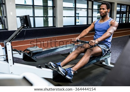 Muscular man using rowing machine at gym