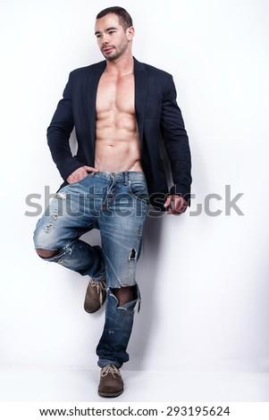 Muscular man wearing fashionable jeans posing in studio . - stock photo