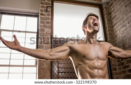 Muscular man with arms stretched at the gym - stock photo