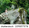 Muscular man with backpack worth on rock in the woods - stock photo