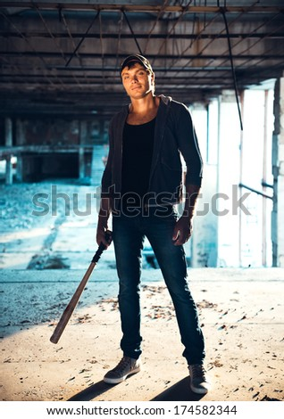Muscular man with baseball bat on the ruins - stock photo