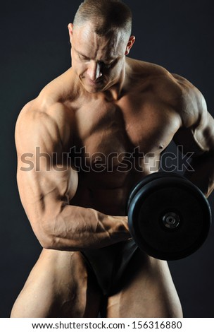Muscular man with dumbbell in studio showing his strong biceps - stock photo