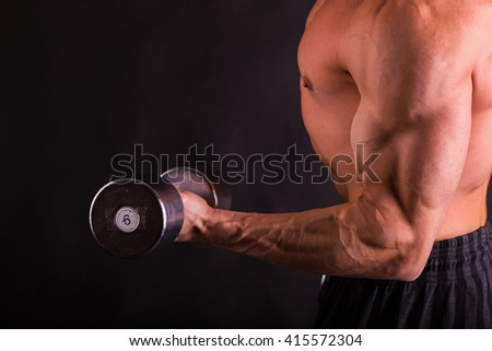 Muscular man with dumbbells on black - stock photo