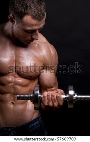 Muscular man with dumbbells on black background.