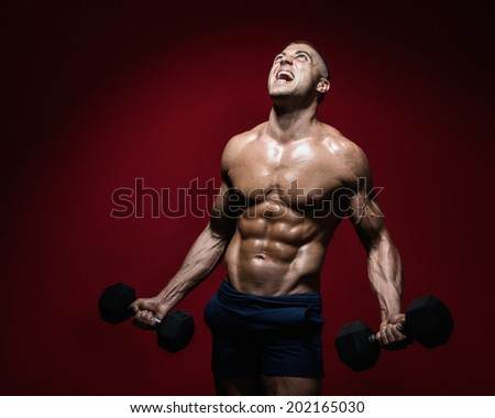 Muscular man with dumbbells screaming out in pain/Agony - stock photo