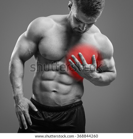 Muscular man with heart pain over gray background. Concept with highlighted glowing red spot. - stock photo