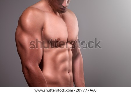 Muscular man with naked chest posing in studio
