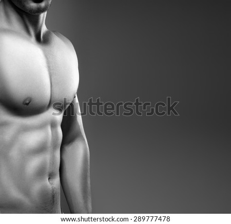 Muscular man with naked chest posing in studio. Photo made in black and white - stock photo