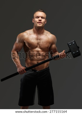 Muscular man with naked torso holding big hummer. Isolated on grey background - stock photo