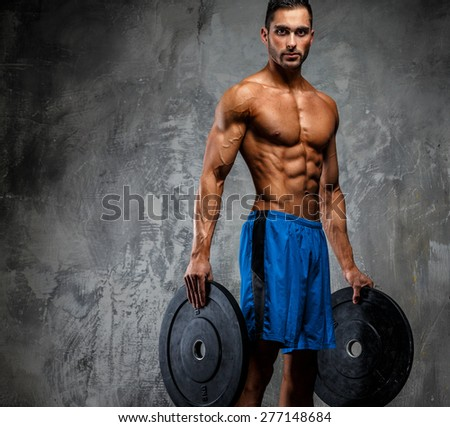 Muscular man with naked torso holding weights. Grey background - stock photo