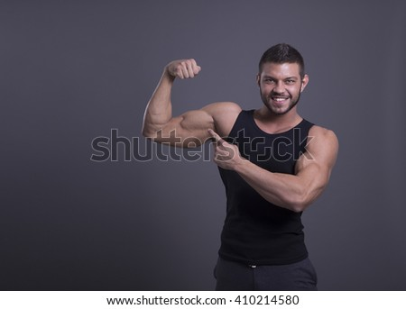 muscular man with perfect body shows his biceps in a black shirt on a dark background
