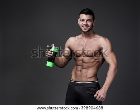 Muscular man with protein drink in shaker over black background