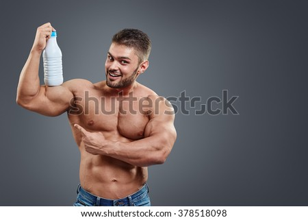 Muscular man with protein drink in shaker over grey background