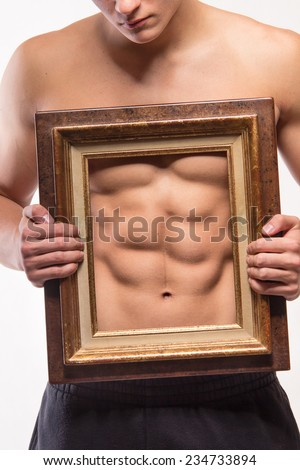 Muscular man with six-pack and frame on his torso - studio shoot - stock photo