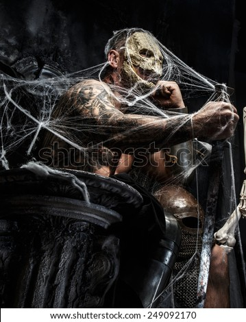 Muscular man with skull on his face and sword in his hand posing on the throne in spiders web on gray background. - stock photo