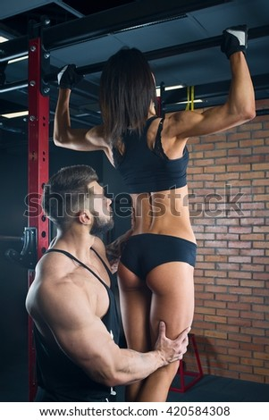 Muscular man with tattoos and beard coaching beauty girl in a black tank top and black shorts in the gym - stock photo