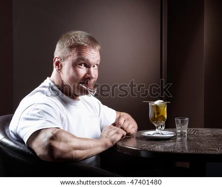 Muscular man with tea - stock photo
