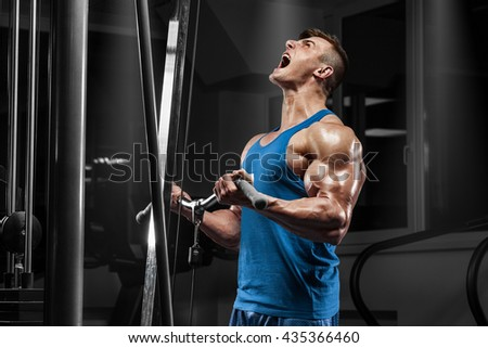 Muscular man working out in gym doing exercises at biceps, strong male - stock photo