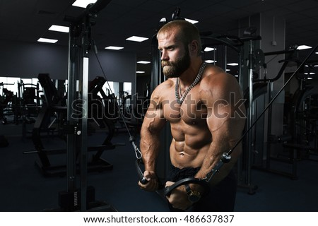Muscular man working out in gym doing exercises at triceps
