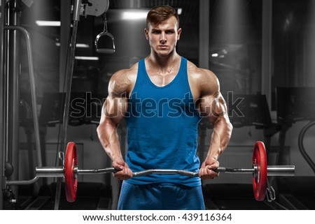 Muscular man working out in gym doing exercises with barbell at biceps, strong male - stock photo