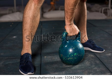 Muscular man working with weights at outdoor