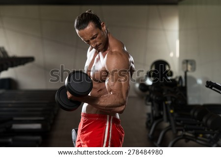 Muscular Mature Man Doing Heavy Weight Exercise For Biceps With Dumbbells In Modern Fitness Center - stock photo