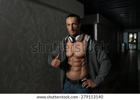 Muscular Mature Man Listening Music From His Mp3 Player In Modern Corridor Where He Poses - stock photo