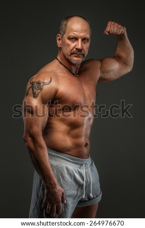 Muscular middle age man posing in studio. Isolated on grey