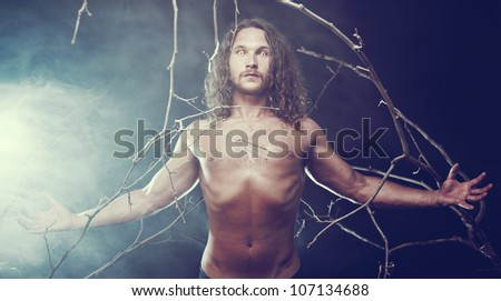 Muscular naked man with scary eyes in the forest, Halloween theme - stock photo