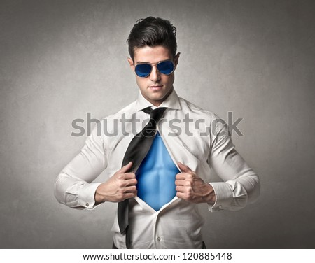 Muscular office worker with sunglasses opening his shirt like a superhero - stock photo