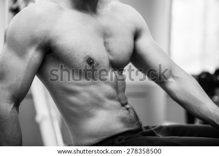 Muscular power athletic male bodybuilder upper body in fitness center. Back and white photo - stock photo