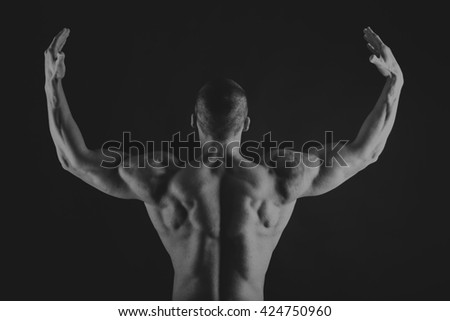 Muscular, relief body bodybuilder on a black background. Black and white photography