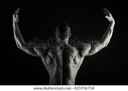 Muscular, relief bodybuilder on a black background - stock photo