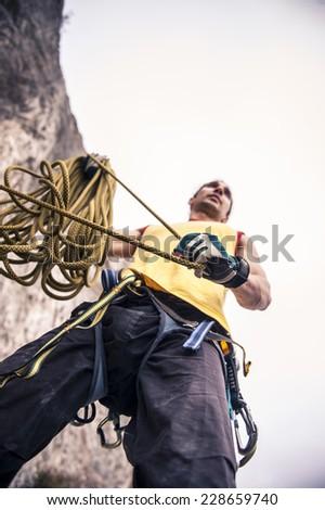 muscular rock climber climbing on a rock. - stock photo